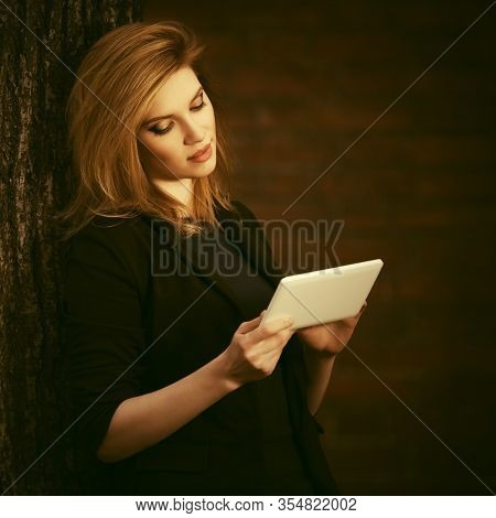 Young fashion blonde business woman using tablet computer  Stylish female model in black blazer