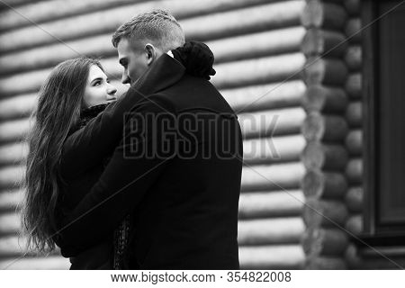 Happy young fashion couple in love embracing outdoor Stylish man and woman in classic coats