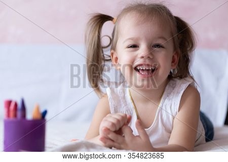 Beautiful Girl Draws With Pencils In Bed. Little Girl Two Years Paints Coloring Book Lying On The Be