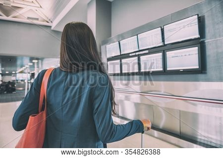 Travel airport tourist woman waiting for delayed flight looking at airport terminal screens showing cancelled flights, corona virus COVID-19 concept. Vacation cancellation from tourism industry.