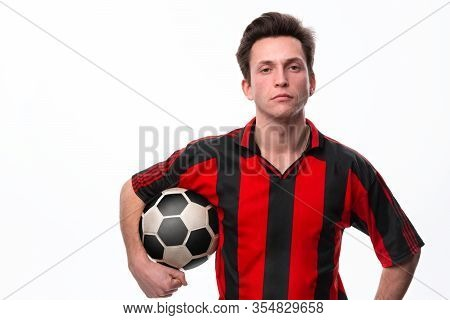 Confident Soccer Player In A Red Sportswear Holding Soccer Ball And Looking At The Camera. Getting R