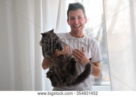 Young Man In The White Shirt And Pajama Is Smiling Holding Fluffy Cat Which Wants To Run Away. Man T