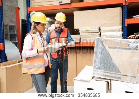 Beautiful Supervisor Examining Box While Checking Inventory With Coworker At Factory