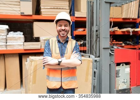 Smiling Handsome Worker Standing With Arms Crossed While Making Eye Contact Against Rack At Warehous