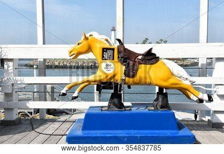 LONG BEACH, CALIFORNIA - 06 MAR 2020: Coin operated horse ride at Shoreline Village at Rainbow Harbor.