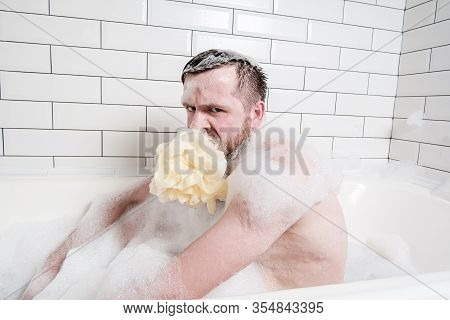 Displeased, Weird Man With A Soapy Sponge Puff In Mouth, Sits In A Bathtub With Lush Foam And Looks