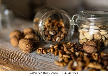 Walnut Scattered On The White Vintage Table From A Jar Whith A Whole Walnuts. Walnut Is A Healthy Ve