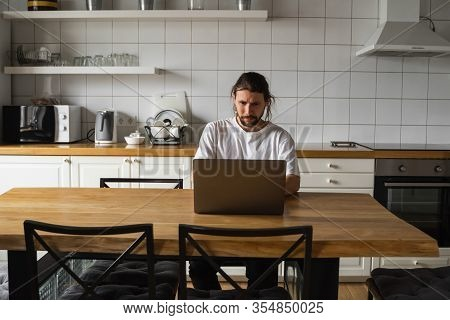 Freelancer Working From Home On The Kitchen And Using Laptop. Bearded Man Working With A Laptop And