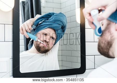 Sleepy Man With A Towel On Head Brushes Teeth With An Electric Brush And Looks With Indifference At