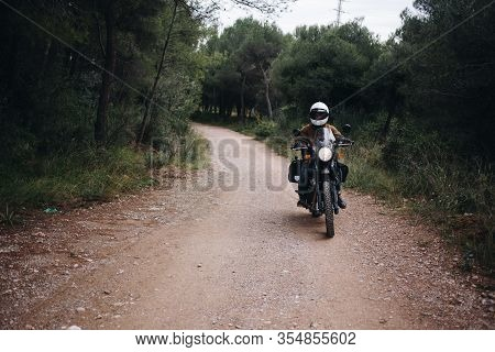 Single Motorcycle Rider On Dirt Road In Forest