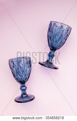 Two Blue Faceted Wine Glasses On A Pink Background