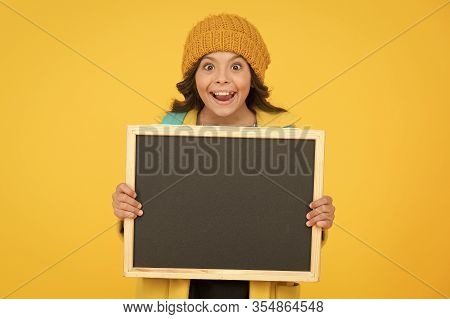 Information Education Materials. Happy Small Child Hold Blank Blackboard For Education On Yellow Bac