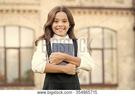 Little Expert In Books. Happy Girl Hold Library Book Outdoor. School Bibliopole. Bibliopole And Bibl