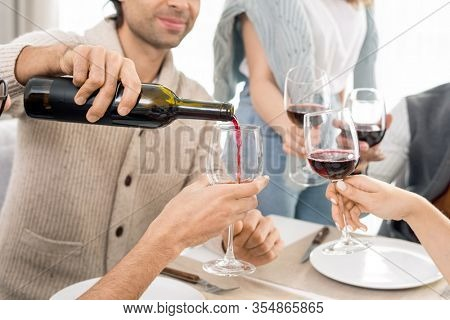 Young man pouring red wine from bottle into wineglasses of his friends while celebrating holiday by served table together