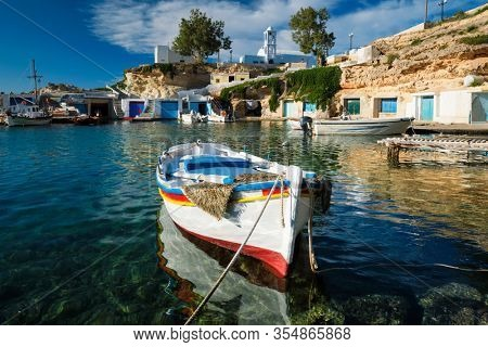 Fishing boars moored in crystal clear turquoise sea water in harbour in Greek fishing village of Mandrakia, Milos island, Greece. Horizontal camera pan