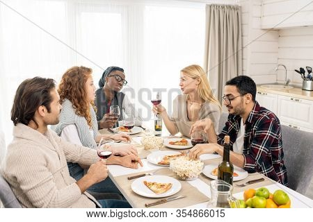 Pretty blond girl with glass of wine sitting among her friends by served table and pronouncing celebratory toast by lunch