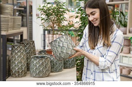 A Beautiful Young Woman In A Flower Shop Chooses A Pot For Flowers . The Concept Of Gardening And Fl