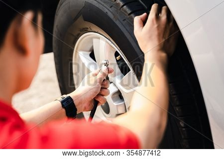 Close Up Of Asian Man Inflating Tire In The Gas Station.