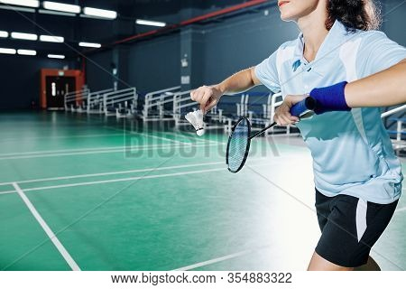 Cropped Image Of Sportswoman Serving Shuttlecock When Playing Badminton In Gymnasium