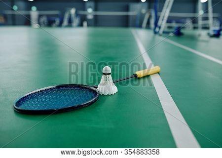 Shuttlecock And Racquet On Gymnasium Floor, Selective Focus