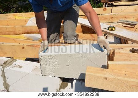 Bricklayer Builder Laying Autoclaved Aerated Concrete Blocks For House Wall Near Unfinished Roof Eav