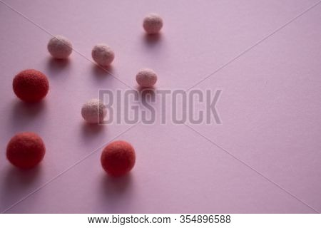 Chaoticly Scattered On A Smooth Smooth Light Pink Surface Are Large And Small Balls Of Felt Of Dark