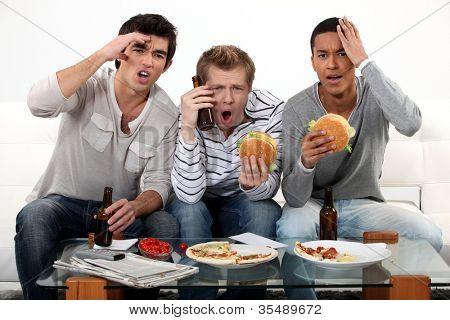 Three lads cringing at the television