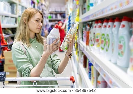 Woman Choosing Detergents In Household Goods Store