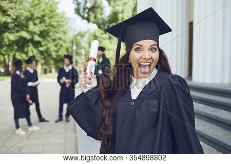 Graduate Girl Smiling Against The Background Of A Group Of Graduates.