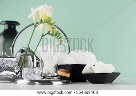 Stylish Dressing Table With Black, Silver Accessories For Skin Care On Green Mint Menthe Wall, White
