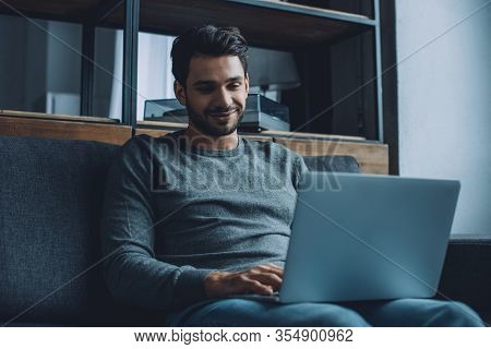 Young Man Smiling While Watching Pornography On Laptop In Living Room