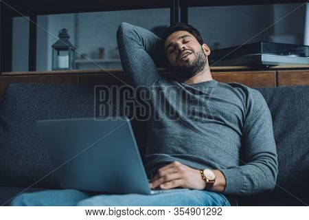 Handsome Man Masturbating While Watching Pornography On Laptop On Couch