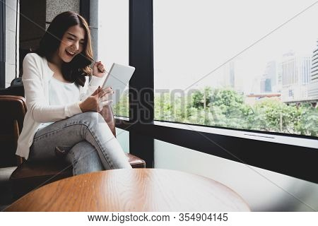 Happy Young Asian Woman Using Digital Tablet And Feeling Happiness While Reading Ebook, Media Book L