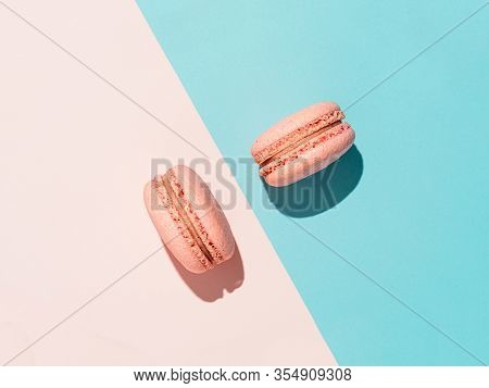 Pink Macarons With Copy Space. Row Of Perfect French Macarons Or Macaroons On Pink And Blue Backgrou