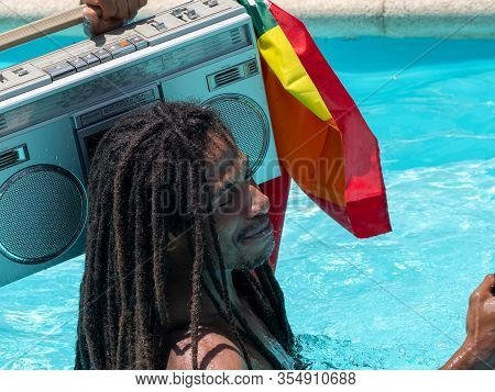 Stock Photo Of A Black Guy With Dreadlocks In The Pool With A Cassette On His Shoulder And Smiling.