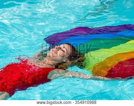 Stock Photo Of A Blonde Girl Lying Relaxed In The Water Of A Swimming Pool With An Lgtb Flag. Lifest