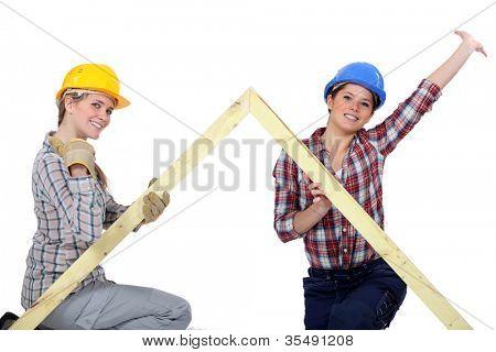 Peppy tradeswomen holding up a wooden frame