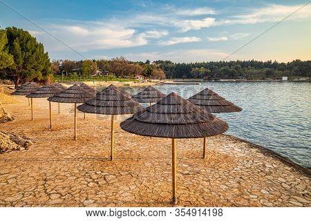 Sunshades On The Beach At The Sunset. The Blue Lagoon In Porec - Istria, Croatia, Europe.