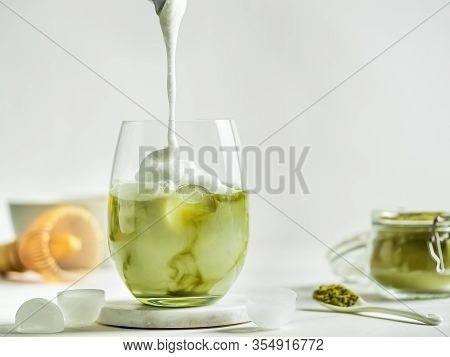 Iced Matcha Latte Tea With Pouring Whipped Cream In Tumbler Glass. Matcha Latte And Ingredients On W