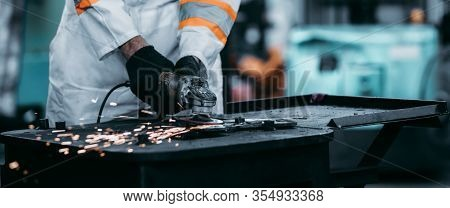 Electric Wheel Grinding On Steel Structure In Factory, Worker With Protective Mask Welding Metal And