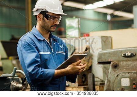 Maintenance Engineer Industrial Plant With A Tablet In Hand And Document Plan, Engineer Looking Of W