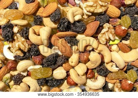 Background Made Of Mixed Nuts And Raisins. Healthy Snack And Food. Cashew, Almond, Raisins, Walnut,