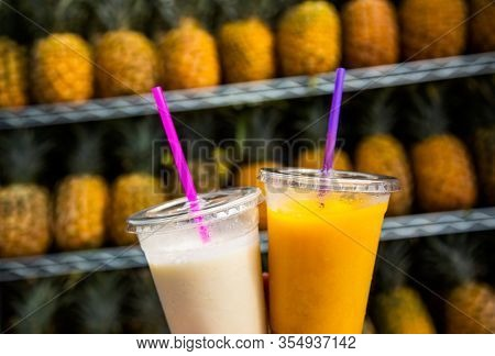 Two glasses of tropical fruit smoothies. Delicious refreshing drinks. Pina Colada and pineapple mango smoothie made from fresh fruit