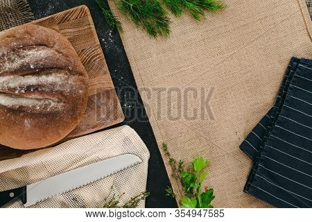 Whole Bread With Canvas, Knife And Green On Black Background. Bulletin Board Concept With Copy Space