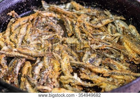 Fried Fish Capelin On Black Frying Pan