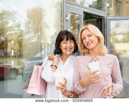 Two Mature Women Having Fun While Doing Shopping And Drinking Coffee