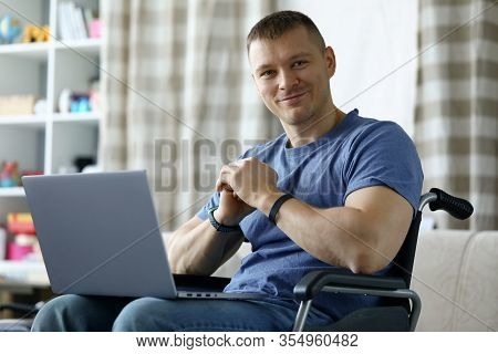 Portrait Of Smiling Disabled Male Sitting In Wheelchair And Working On Laptop From Home. Young Worke
