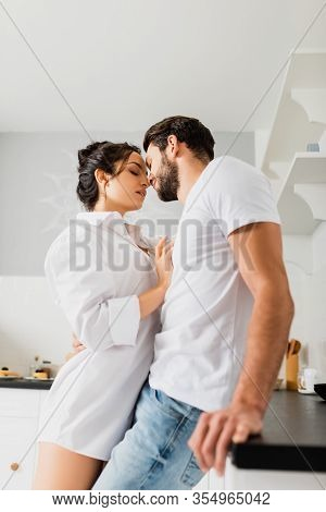 Side View Of Sensual Girl In Shirt Kissing Handsome Boyfriend Near Kitchen Worktop