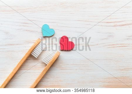 Two Bamboo Toothbrushes, Blue And Red Wood Hearts On Vintage Wood Background. Biodegradable Bamboo T