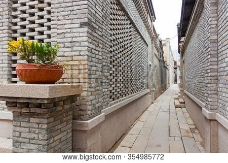A characteristic alley of the retro style Chinese village, with brick houses and flagstone pavement, flower on pot decorated in entrance, Fuzhou,Fujian,China